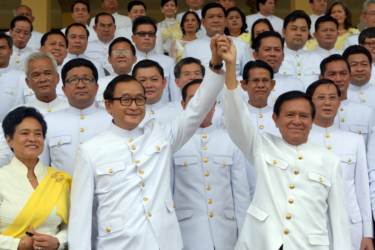 Cambodian opposition leader Sam Rainsy (front left) raises hands with Kem Sokha in 2014. Photo: AFP / Tang Chhin Sothy