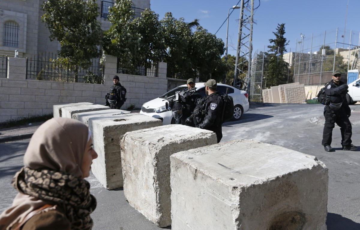Israeli security forces stand next to newly-installed concrete blocks in the predominantly Palestinian East Jerusalem neighbourhood of Jabal Mukaber on December 9 2016, a day after a Palestinian from the area committed a truck ramming attack, killing four Israeli soldiers. Photo: AFP