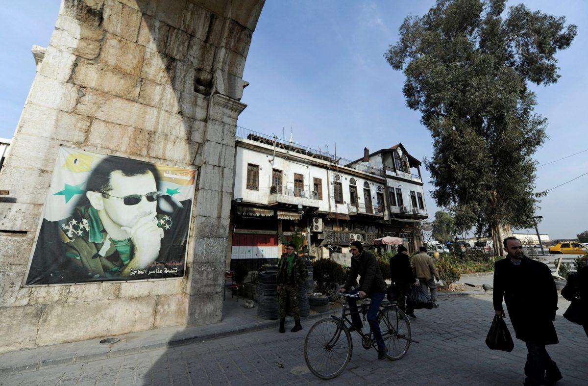 People walk past a picture of Syria's President Bashar al-Assad at Bab Sharqi entrance, near the Jobar district of Damascus, Syria, January 5, 2017. REUTERS/Omar Sanadiki