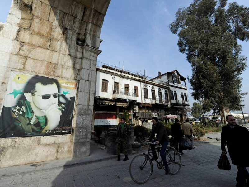 People walk past a picture of Syria's President Bashar al-Assad at Bab Sharqi entrance, near the Jobar district of Damascus, Syria, January 5, 2017. REUTERS/Omar Sanadiki