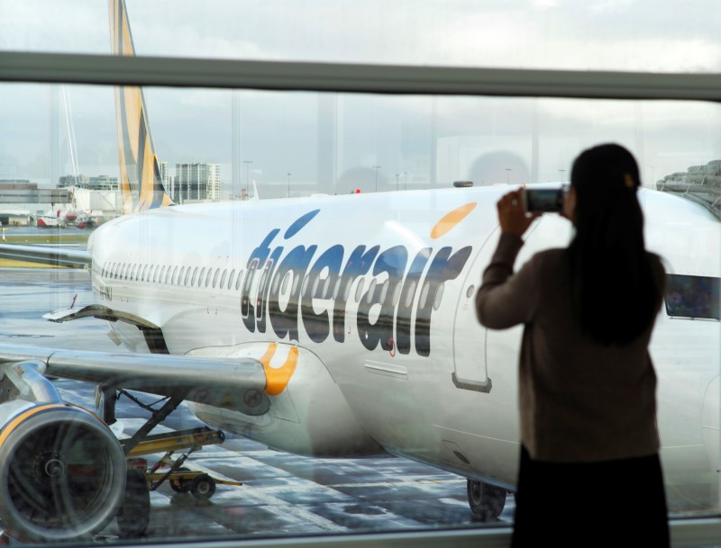 A passenger takes a photo of a Tigerair jet at Sydney's Airport in Australia. Photo:  Reuters/Jason Reed