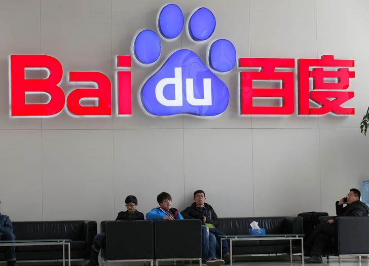 People sit in front of the company logo of Baidu at its headquarters in Beijing December 17, 2014. REUTERS/Kim Kyung-Hoon/File photo