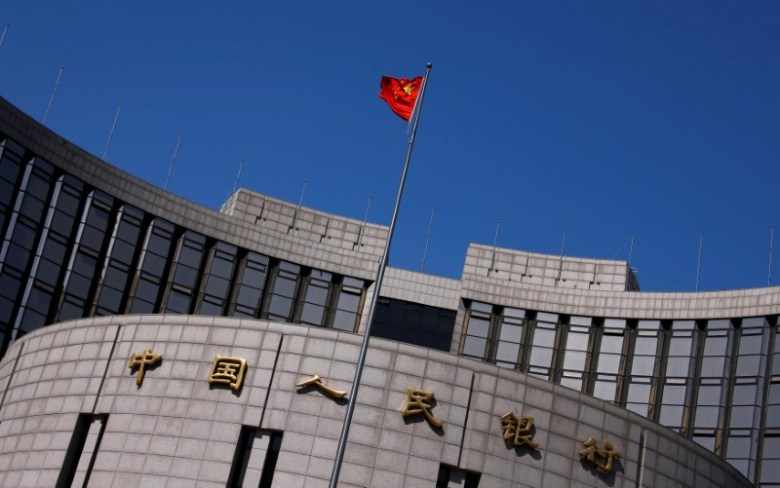 A Chinese national flag flutters outside the headquarters of the People's Bank of China, the Chinese central bank, in Beijing, China April 3, 2014.   REUTERS/Petar Kujundzic/File Photo