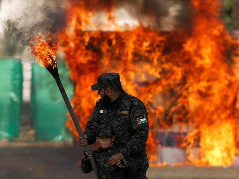 A Palestinian boy uses a torch to burn a mock Israeli army post as part of a drill during a graduation ceremony for members of Palestinian National Security Forces loyal to Hamas, in Gaza City, on January 22, 2017. Photo: Reuters