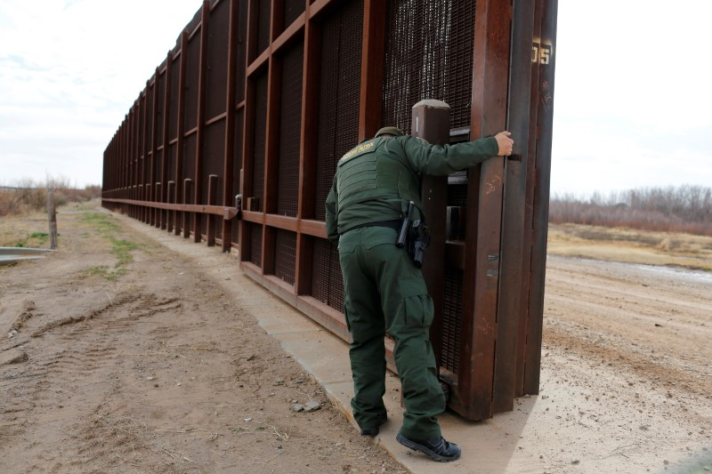 A US Border patrol agent opens a gate on the fence along the Mexico border. Photo: Reuters/Tomas Bravo