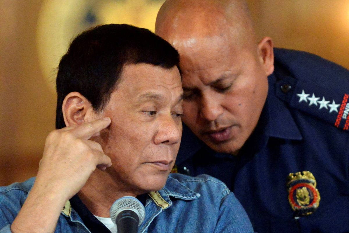 Philippine President Rodrigo Duterte (L) listens to Philippine National Police (PNP) Director General Ronald Dela Rosa during a late night news conference at the presidential palace in Manila, Philippines January 29, 2017. Reuters/Ezra Acayan