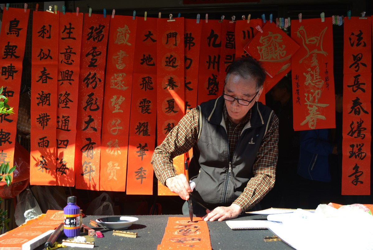 A calligrapher writes a set of spring festival couplets for a customer. Spring festival couplets are used as New Year decorations in Taiwan to express hopeful thoughts for the coming year. Handwritten ones are increasingly rare in the digital age. Photo: Asia Times / Liu Hsiu Wen
