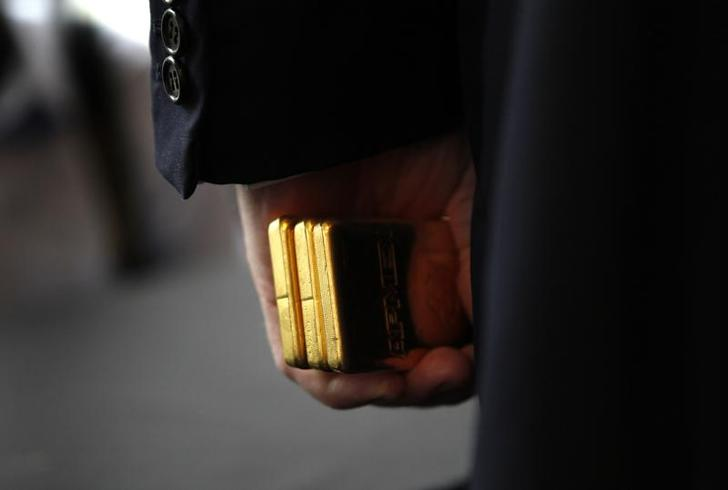 Developer Donald Trump holds three bars of Gold Bullion after accepting it as a security deposit from the American Precious Metals Exchange (APMEX) for a 10 year lease for APMEX on the 50th floor of 40 Wall Street in New York City, a Trump owned property, during a news conference in New York, September 15, 2011.   REUTERS/Mike Segar    (UNITED STATES - Tags: BUSINESS REAL ESTATE)