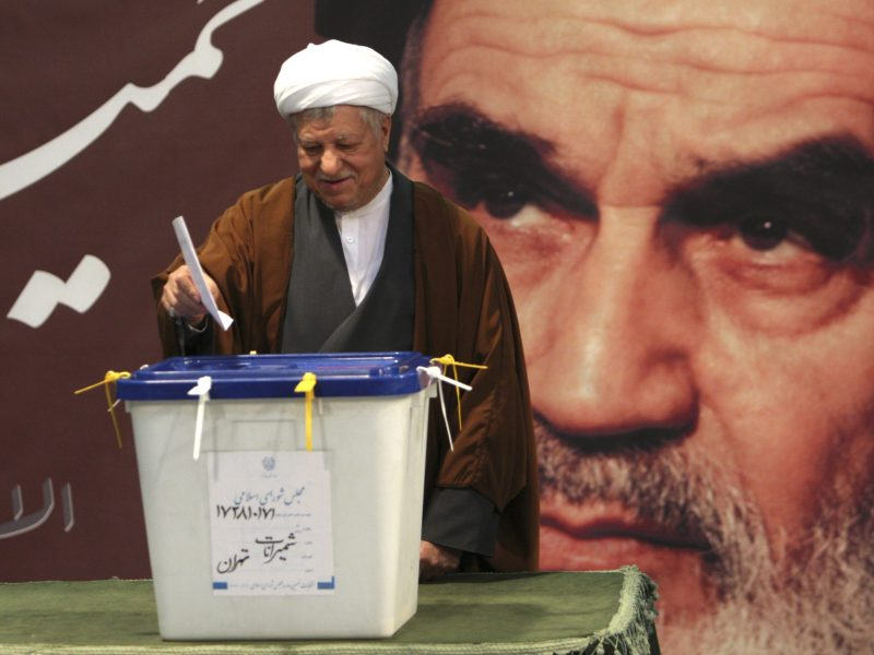 Struggling to escape Khomeini's shadow: Former Iranian president Akbar Hashemi Rafsanjani casts his ballot in a 2012 parliamentary election in Tehran, with an image of Ayatollah Ruhollah Khomeini, the late founder of the Islamic Republic, looming behind him. Photo: Reuters/Stringer