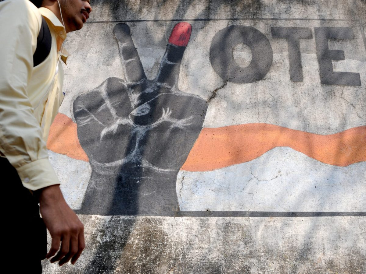 A pedestrian walks past graffiti urging Indians to vote in Mumbai. Photo: AFP/Indranil Mukherjee
