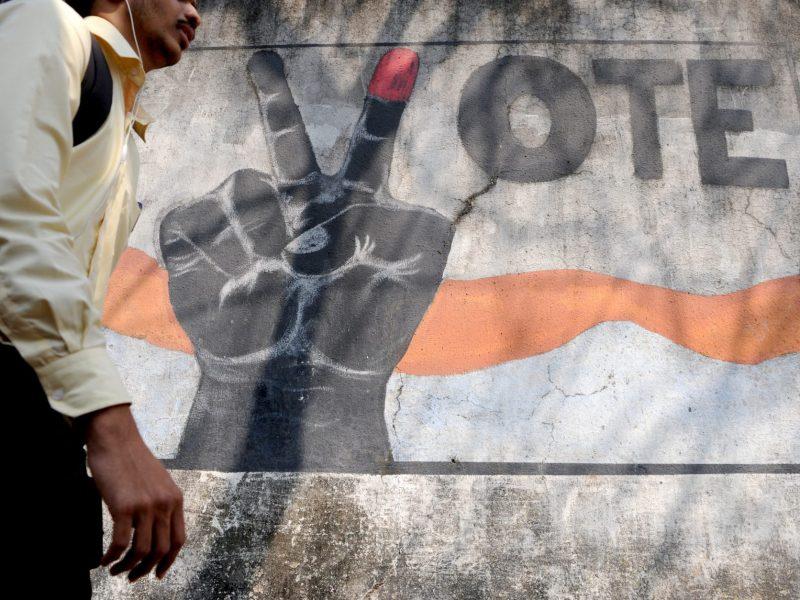 A pedestrian walks past graffiti urging Indians to vote in Mumbai. Photo: AFP/Indranil Mukherjee
