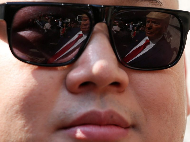 Trump impersonator Dennis Alan of Chicago, 66, is reflected in the sunglasses of Kim lookalike, Australian-Chinese Howard, 37. Photo: Reuters/Bobby Yip