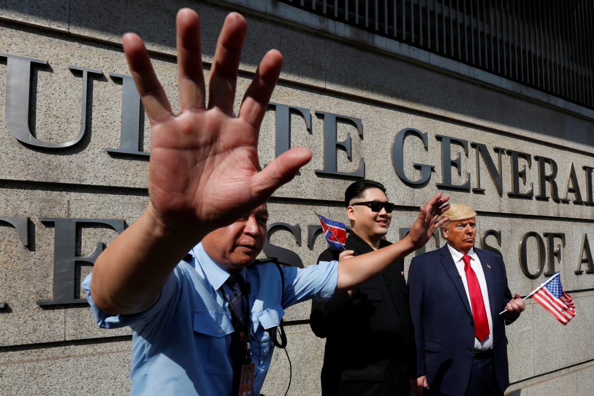 A security guard intervenes as Howard, 37, an Australian-Chinese who is impersonating North Korean leader Kim Jong-un, and Dennis Alan of Chicago, 66, who is impersonating President Donald Trump, pose outside US Consulate in Hong Kong. Photo: Reuters/Bobby Yip