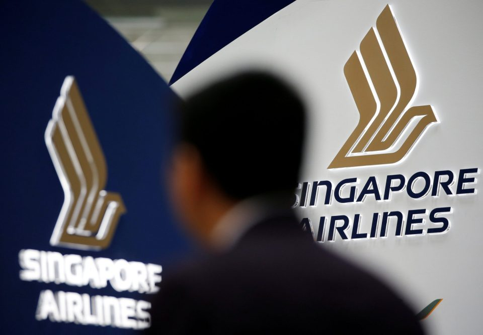 FILE PHOTO -  A man walks past a Singapore Airlines signage at Changi Airport in Singapore May 11, 2016. REUTERS/Edgar Su/File Photo                        GLOBAL BUSINESS WEEK AHEAD PACKAGE - SEARCH 'BUSINESS WEEK AHEAD 6 FEB'  FOR ALL IMAGES