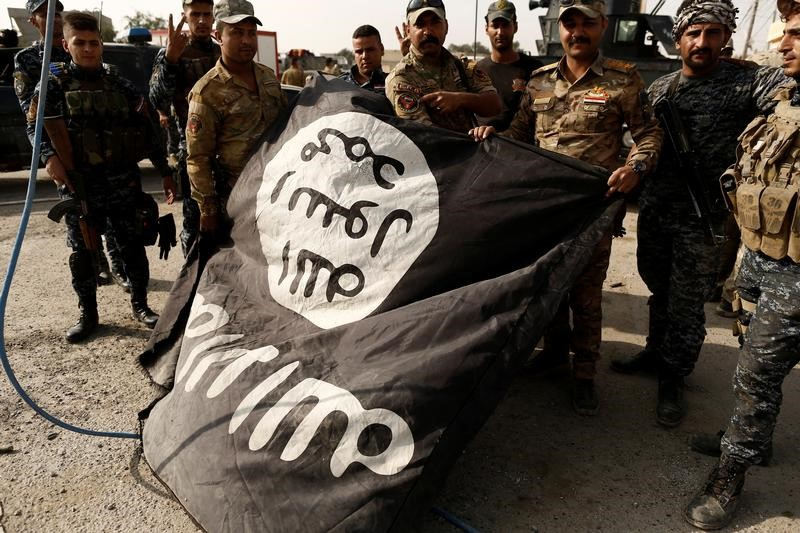 Iraqi soldiers pose with the Islamic State flag. Photo: Reuters, Zohra Bensemra