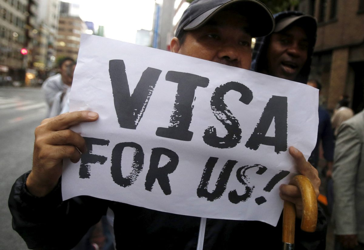 FILE PHOTO: A protester holding a placard shouts slogans at a rally to call for visa grants for asylum seekers in Japan, in central Tokyo, September 9, 2015.REUTERS/Yuya Shino/File Photo