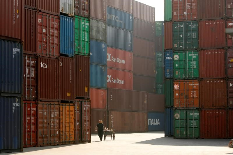 FILE PHOTO -  A woman walks past containers at a port in Shanghai. Photo: Reuters / Aly Song