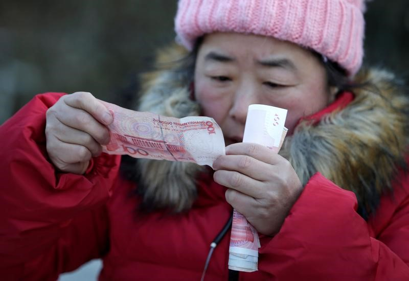 A woman looking at a yuan note Photo: Reuters