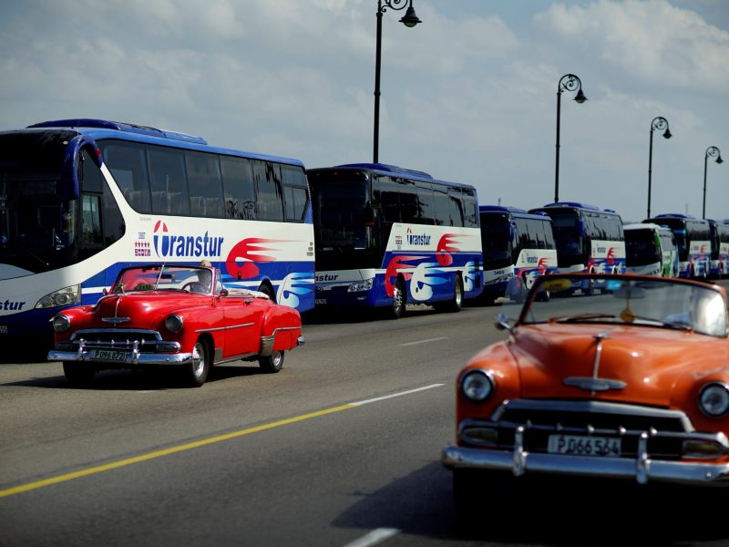 Vintage cars pass by a fleet of Chinese-made Yutong buses parked at the sea front Malecon in Havana, Cuba, February 10, 2017. Picture taken February 10, 2017.  REUTERS/Alexandre Meneghini