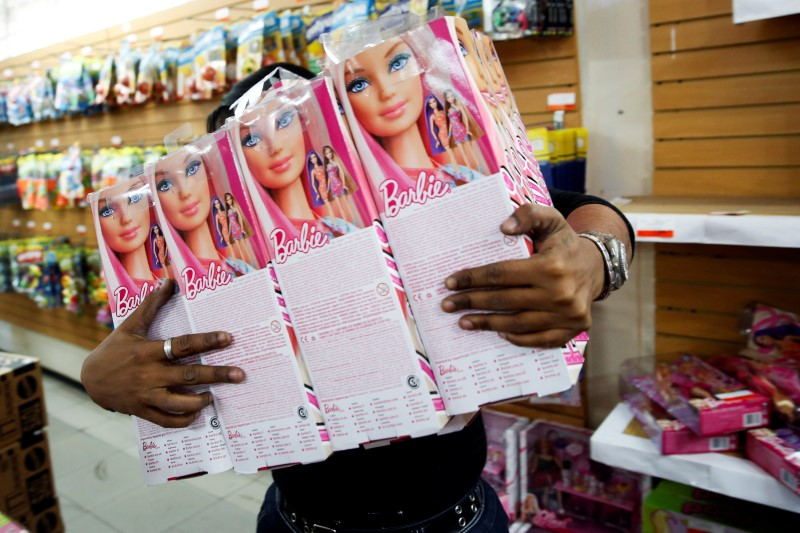 A worker carries Barbie dolls to put them on the shelves at a toy store in Caracas November 14, 2014. Photo: REUTERS/Carlos Garcia Rawlins