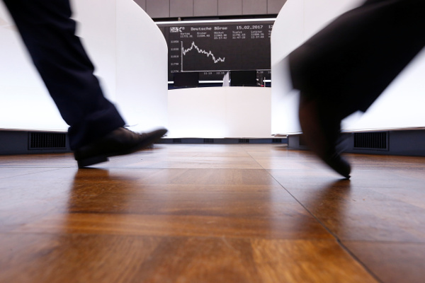 Traders walk past German DAX Index board. Photo: Reuters/Ralph Orlowski