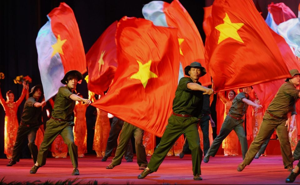 Performers dance with large national flags marking an anniversary of Vietnam's communist regime in Hanoi, February 3, 2017.  Photo: AFP/Hoang Dinh Nam