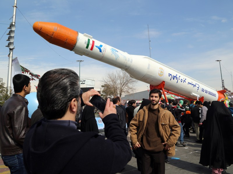 Iranians take pictures of a satellite rocket during celebrations in Tehran to commemorate the Islamic Revolution. Photo: Atta Kenare, AFP