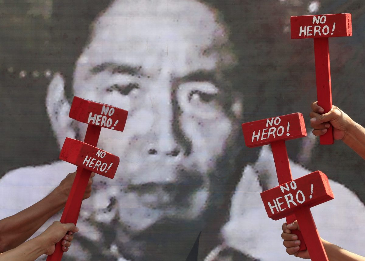 Protestors hold mock hammers with words 'No Hero' in front of a portrait of the late dictator Ferdinand Marcos as they denounce his burial at the Libingan ng mga Bayani (Heroes' cemetery) during a protest outside the presidential palace in metro Manila, Philippines November 22, 2016. REUTERS/Romeo Ranoco - RTSSQLS