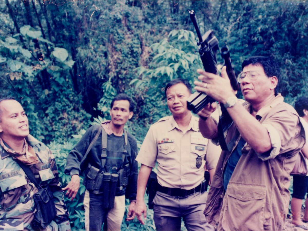 Rodrigo Duterte, then mayor of Davao City, now president of the Philippines, inspects the assault rifle of an official at a crime scene in the village of Tamugan in Davao City in the southern Philippines in 1997. Looking on is then Davao Police Chief Isidro Lapena (2nd, R). Picture: Reuters / Lenato Rumawag
