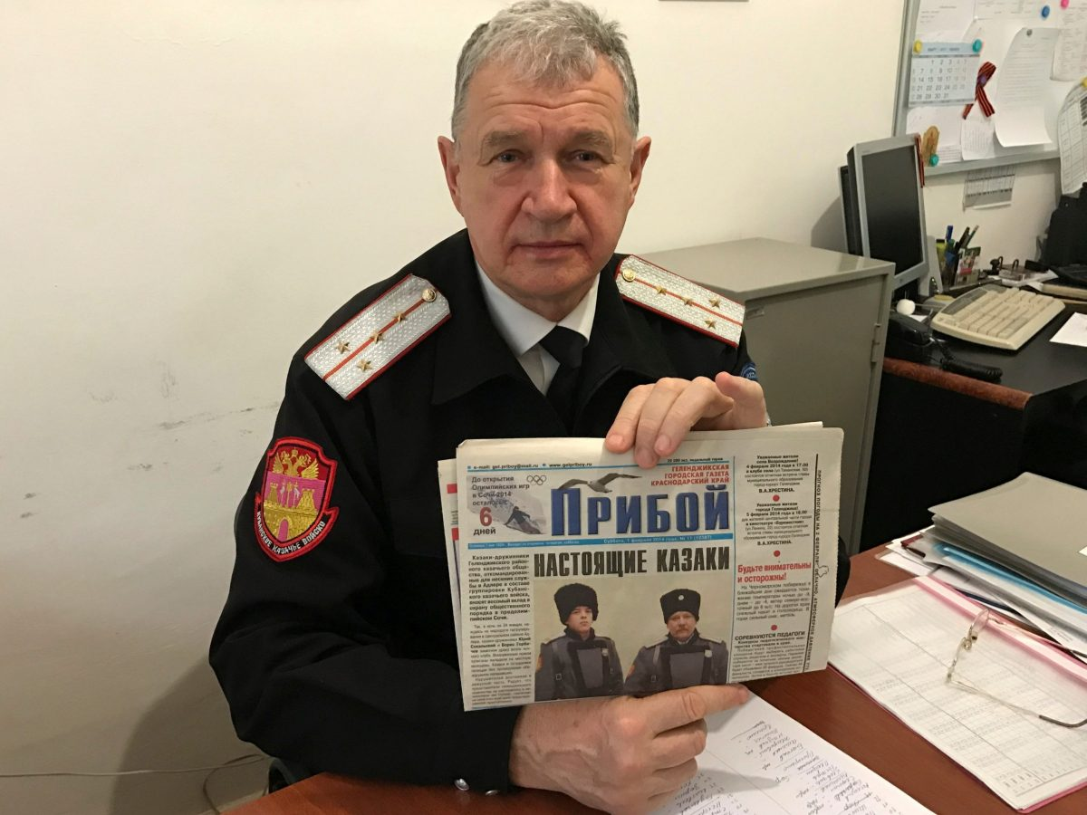 Russian Cossack commander Vladimir Bagliy shows a local newspaper with a picture of his fellow Cossack Yuri Sokalsky (R) killed near the Syrian city of Palmyra, in the Black Sea town of Gelendzhik. Photo: Reuters