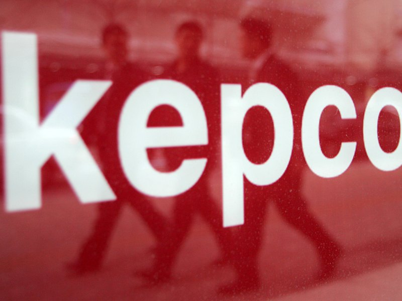 South Koreans are reflected in a company sign for Korea Electric Power Corp in Seoul February 18, 2005.   Reuters/You Sung-Ho