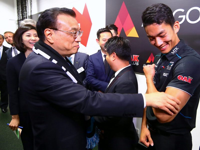 Chinese Premier Li Keqiang touches the arm of Port Adelaide player Chen Shaoliang, the Australian rules football club's international academy recruit from China, on March 25, 2017. Photo: Reuters / David Gray