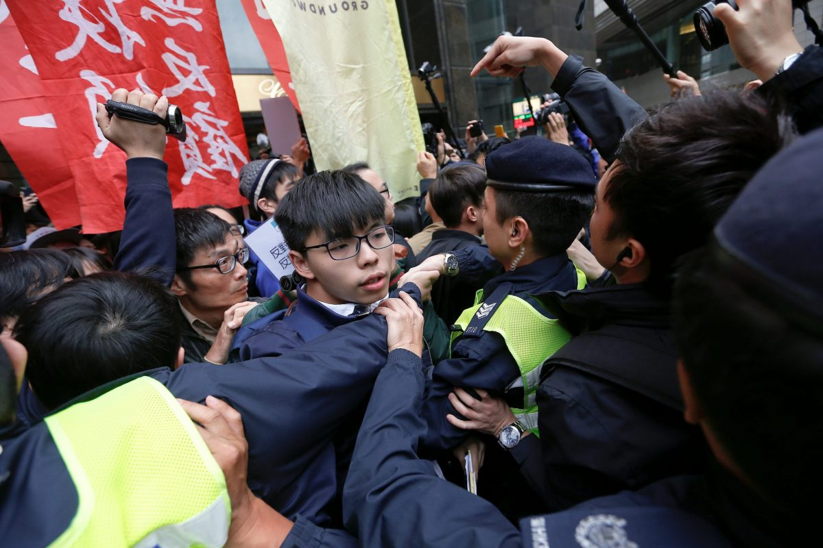 Hong Kong democracy activist Joshua Wong and others scuffle with police as they protest during the election.  Photo: Reuters/Tyrone Siu
