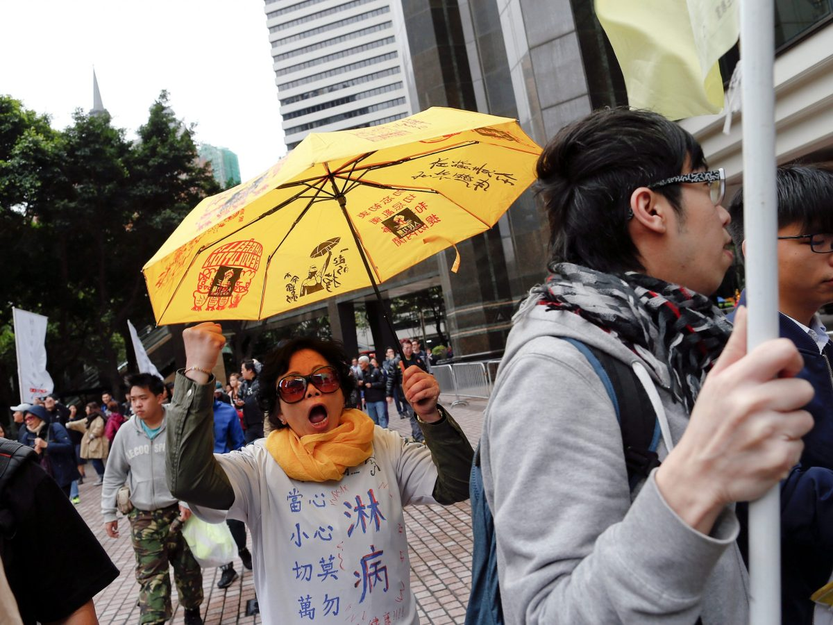 Voicing her anger. A woman holds up a yellow umbrella, the symbol of the Occupy Central movement, as she and others protest during the election for Hong Kong's next Chief Executive. Photo:  Reuters/Tyrone Siu
