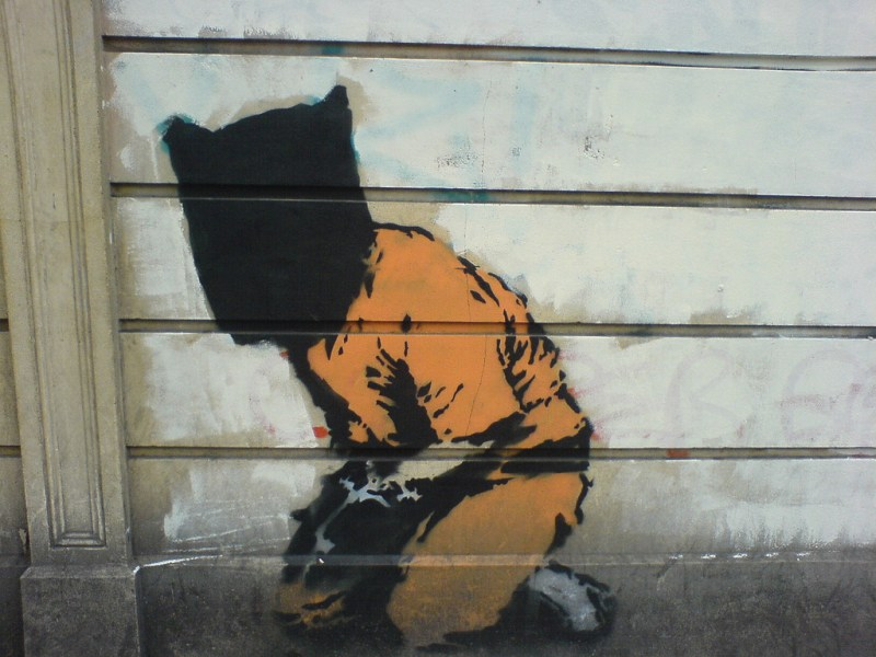 Guantanamo Bay just won't go away. Photo of Banksy painting via Wikimedia Commons