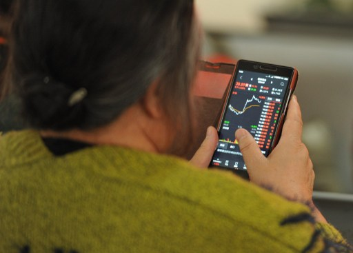 A Chinese investor looks at prices of shares on her smartphone. Photo: AFP