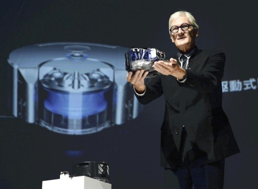 """James Dyson, a founder of  Dyson Ltd., shows a new  robotic vacuum cleaner, called  """"Dyson 360 Eye,"""" in Minato Ward,  Tokyo. Photo: AFP, The Yomiuri Shimbun"""