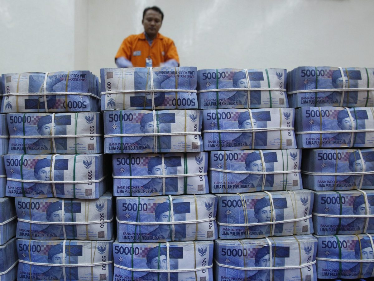 A worker removes bundles of rupiah banknotes at the headquarter of the state-owned Bank Negara Indonesia (BNI) headquarters, in Jakarta. Photo: Reuters / Supri