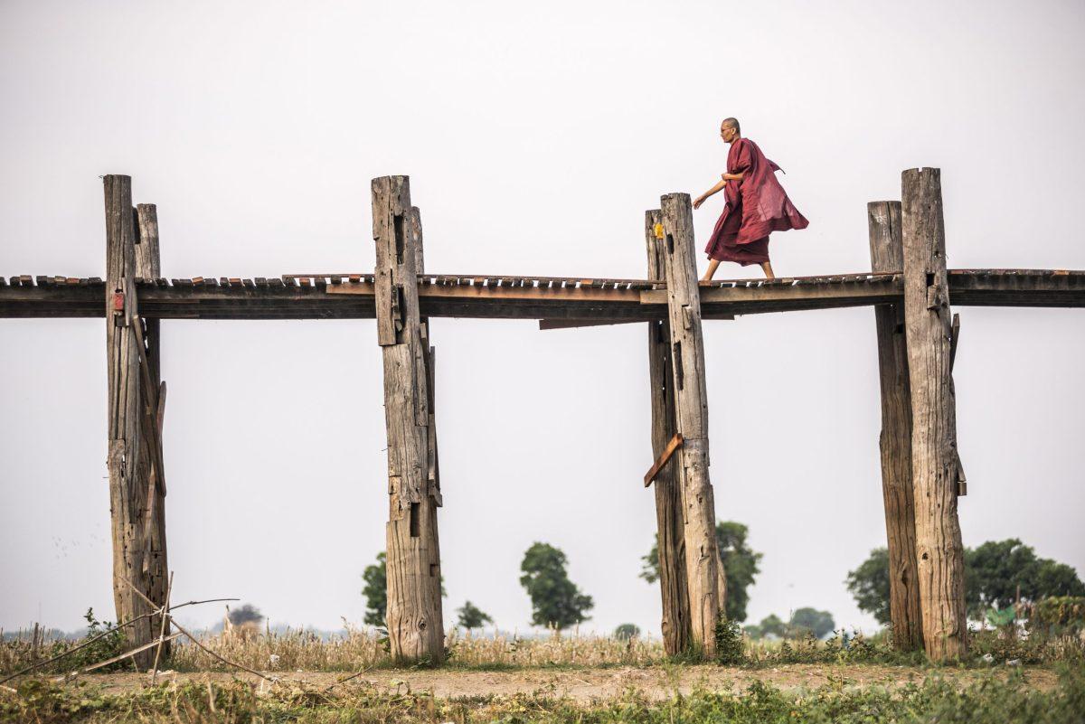A Buddhist Monk walks along a 1.2 kilometer wooden bridge in Mandalay, central Myanmar. Photo: AFP Forum