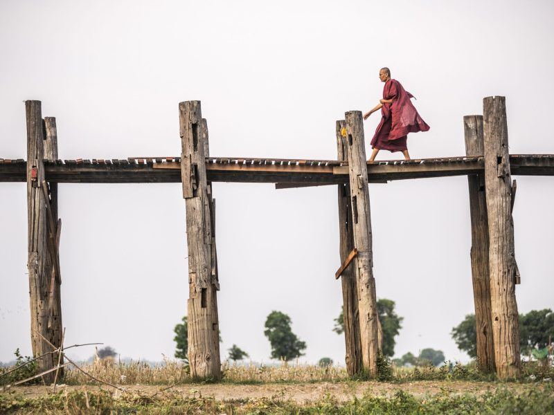 A Buddhist Monk walks along a 1.2 kilometer wooden bridge in Mandalay, central Myanmar. Photo: AFP Forum
