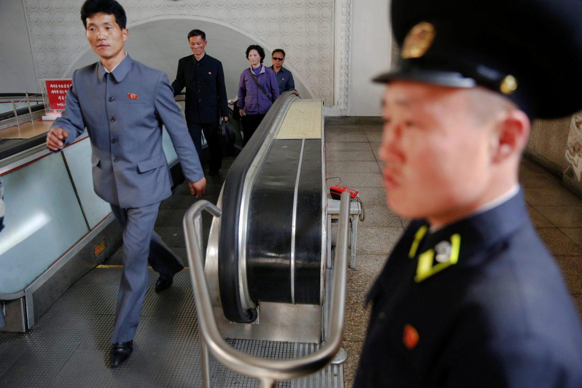 A subway worker stands at the end of escalators in Pyongyang, North Korea. Photo: Reuters, Damir Sagolj
