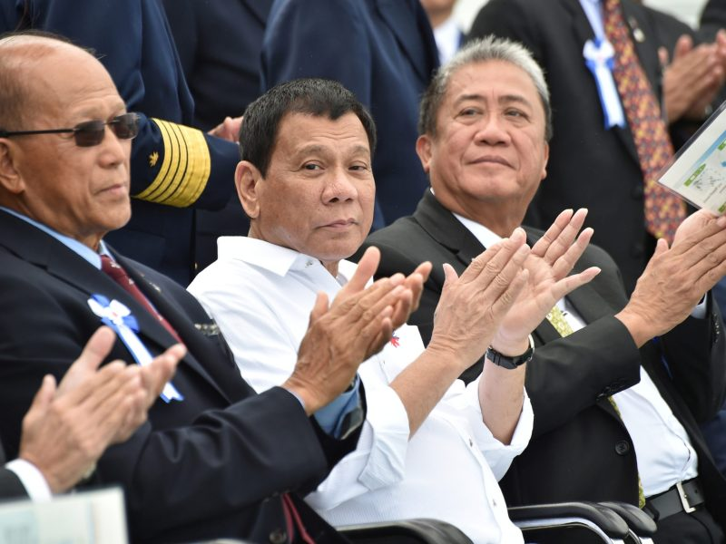 Philippine President Rodrigo Duterte (C), accompanied by Transportation Secretary Arthur Tugade (R) and Defense Secretary Delfin N Lorenzana (L), claps at the end of Japan's coast guard drills in Yokohama, Japan October 27, 2016. REUTERS/Kazuhiro Nogi
