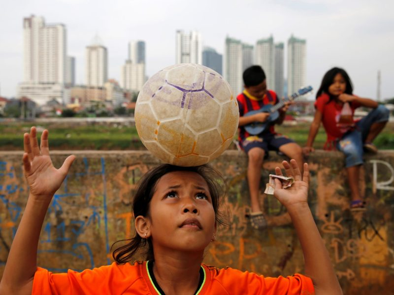 A girl plays football in the park beside a concrete flood wall in Jakarta, Indonesia, August 4, 2016. REUTERS/Beawiharta - RTSL12O