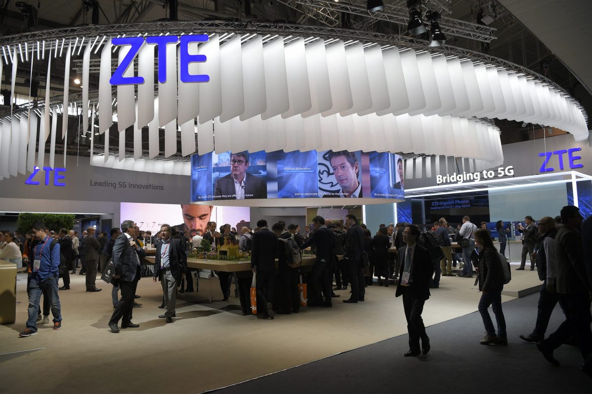 Visitors pass in front of the ZTE stand at the Mobile World Congress. Photo: AFP