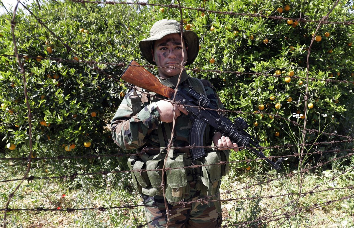 A Hezbollah fighter on patrol in an orange orchard near the town of Naqura on the Lebanese-Israeli border on April 20. مقاتل بحزب الله يقوم بالحراسة بجانب مدينة ناقورة على الحدود اللبنانية الإسرائيلية في 20 إبريل/نيسان.Photo: AFP
