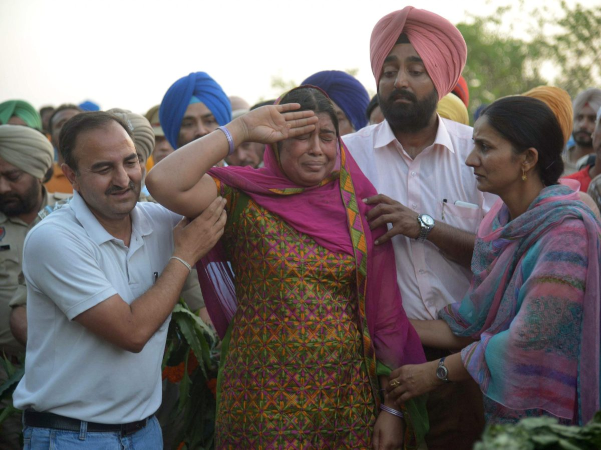 Baljit Kaur (center) salutes after laying a wreath on the pyre of her husband Raghbir Singh, a CPFR officer killed by Maoists on Monday. Photo: AFP
