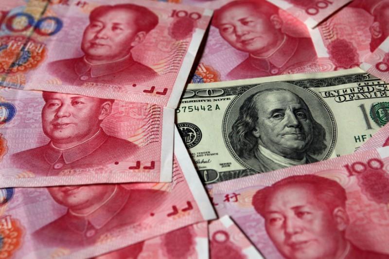 A US dollar note amid the 100 yuan notes. Photo: Reuters/Petar Kujundzic