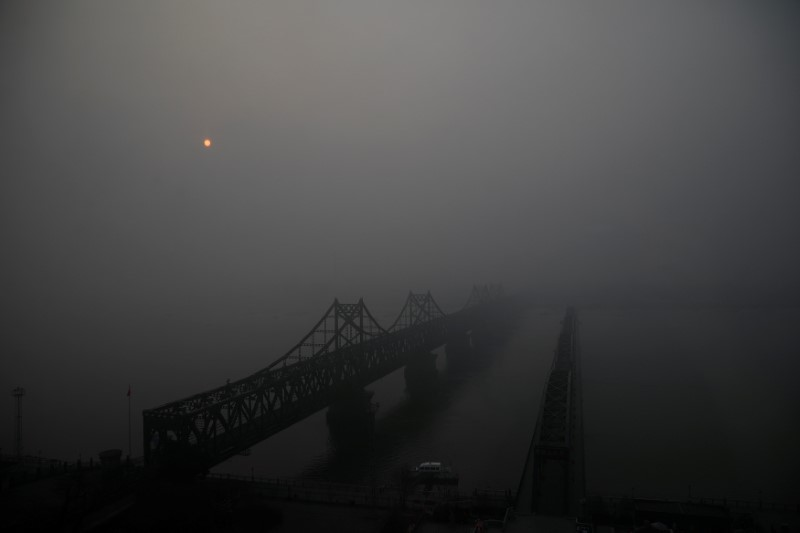The sun rises through fog over the Friendship and the Broken bridges over the Yalu River connecting the North Korean town of Sinuiju and Dandong in China's Liaoning province, March 30, 2017. Reuters/Damir Sagolj