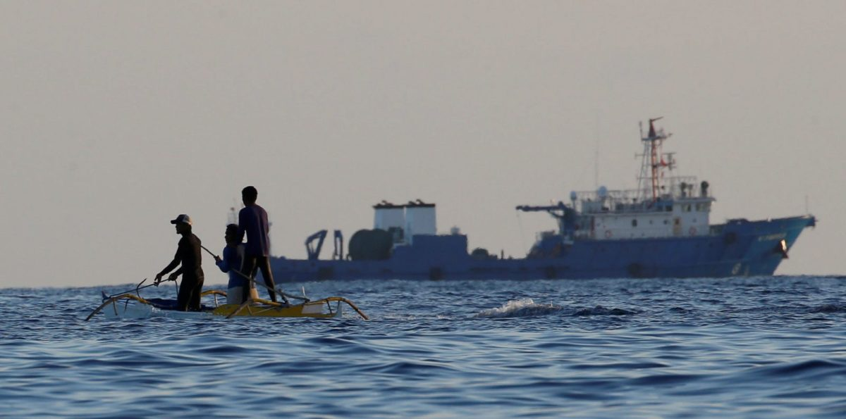 Filipino fishermen pass by a large Chinese vessel at the disputed Scarborough Shoal. Photo: Reuters/Erik De Castro