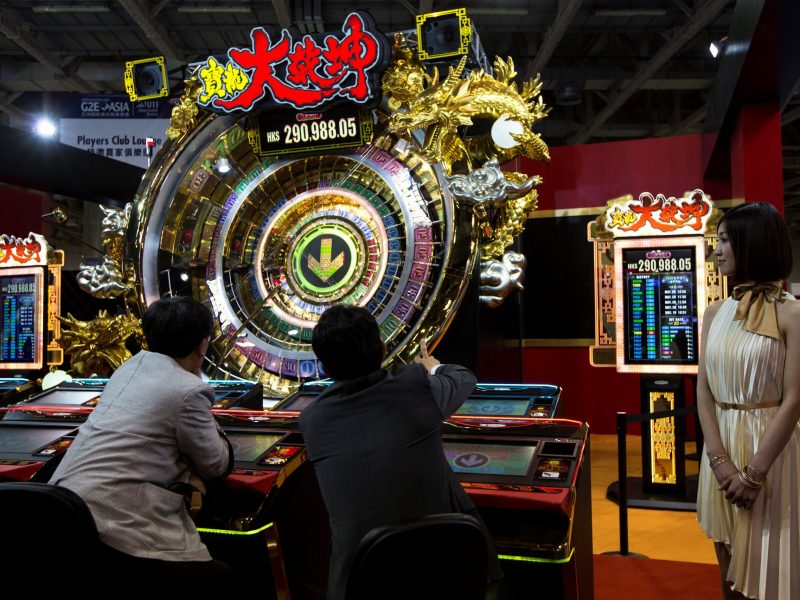 Visitors sit in front of lucky wheels made by the Japanese company Sega Sammy Creation, at the Global Gaming Expo Asia in Macau, on April 19, 2017. Photo: Reuters / Tyrone Siu